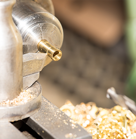 A brass stone setting being turned on a lathe