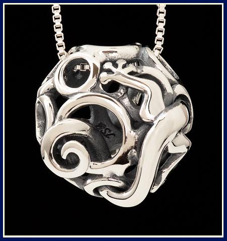 sculptural lizard peaking out of filigree bead in sterling silver