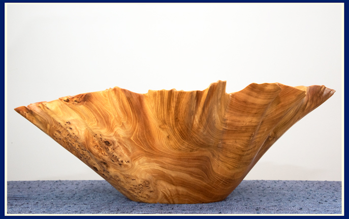 side view of elm burl wooden bowl with ruffled edge