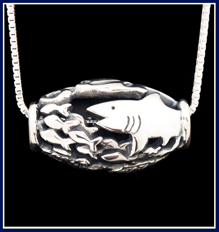 a shark chasing fish on a sterling silver bead by Jeni Benos